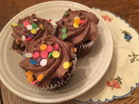 Three tiny cupcakes with colorful sprinkles.