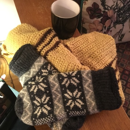 Scarf and mittens resting near a cup for coffee