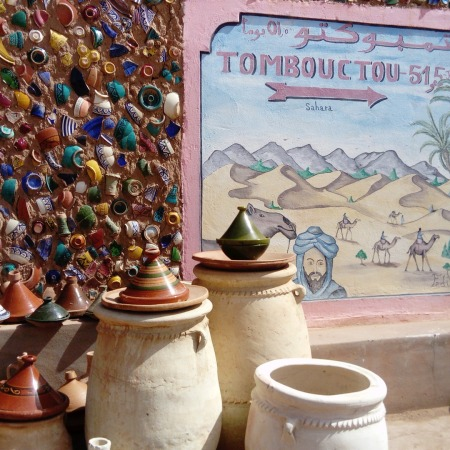 ceramic teapots surrounding a sign with directions to Timbuktu