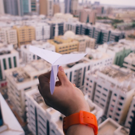 Paper airplane in hand ready to send over a city