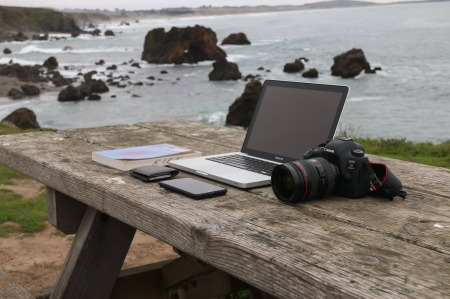 camera, laptop, phone, coding book, seashore