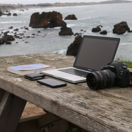 camera, laptop, phone, coding book, seashore